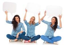Trois jeunes femmes riantes tenant des bulles de la parole et s'asseyent Photo libre de droits