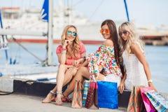 Trois jeunes femmes, s'asseyant sur un banc dans la ville Photo libre de droits