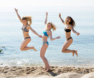 Trois jeunes femmes sautant sur la plage sablonneuse Images libres de droits