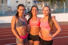 Trois jeunes femmes se tenant ensemble et souriant dans le stade Photos stock
