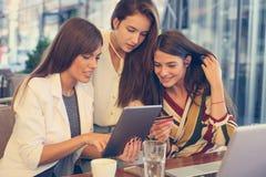 Trois jeunes femmes sur la pause-café observant quelque chose sur l'Internet Photographie stock libre de droits