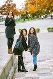 Trois jeunes filles attirantes ayant l'amusement prenant des photos ensemble sur la promenade de ville Un mode de vie Photo libre de droits