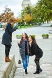 Trois jeunes filles attirantes ayant l'amusement prenant des photos ensemble sur la promenade de ville Un mode de vie Images stock