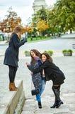Trois jeunes filles attirantes ayant l'amusement prenant des photos ensemble sur la promenade de ville Un mode de vie Photos libres de droits