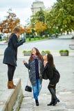 Trois jeunes filles attirantes ayant l'amusement prenant des photos ensemble sur la promenade de ville Un mode de vie Photographie stock libre de droits