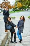 Trois jeunes filles attirantes ayant l'amusement prenant des photos ensemble sur la promenade de ville Un mode de vie Photo stock