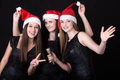Trois jeunes filles attirantes de Santa avec le microphone Photos libres de droits