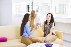 Trois jeunes filles célébrant avec le champagne Image stock