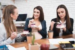Trois jeunes filles mignonnes mangeant le gâteau doux à l'heure du déjeuner dans le bureau Pause de midi Photo libre de droits