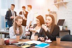 Trois jeunes filles mignonnes mangeant le gâteau doux à l'heure du déjeuner dans le bureau Pause de midi Photos stock