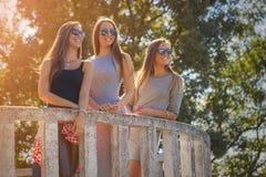 Trois jeunes filles riant et ayant l'amusement dehors Images stock