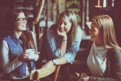 Trois jeunes filles s'asseyant en café et ayant la conversation Photographie stock
