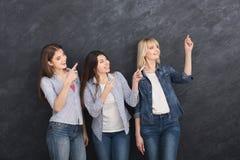 Trois jeunes filles se dirigeant sur le fond gris photos stock