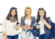 Trois jeunes filles se tenant avec le bagage à l'aéroport et regardant le téléphone Un voyage avec des amis Images stock