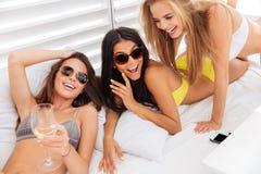 Trois jeunes filles sexy de sourire se trouvant sur le lit blanc Photographie stock libre de droits