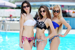 Trois jeunes filles sur le fond de la piscine Photos stock