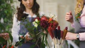 Trois jeunes fleuristes beaux de chef travaillent aux fleurs portent des fruits boutique faisant le bouquet de fruits et légumes banque de vidéos