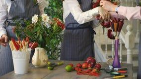Trois jeunes fleuristes beaux de chef travaillent aux fleurs portent des fruits boutique faisant le bouquet de fruits et légumes clips vidéos