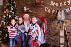 Trois jeunes garçons racontent à Santa Claus des histoires drôles dedans décorés dedans Image stock