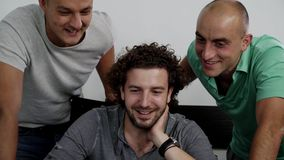 Trois jeunes hommes attirants regardent l'ordinateur portable et rient joyeux ensemble banque de vidéos