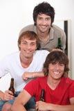 Trois jeunes hommes avec de la bière image stock