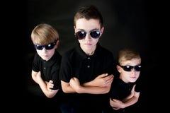 Trois jeunes hommes dans le noir Images stock