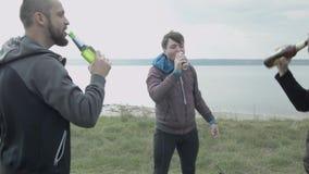 Trois jeunes hommes en nature se cognent dans la bière et la boisson Célébrez la victoire banque de vidéos
