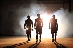 Trois jeunes hommes enfermant dans une boîte la séance d'entraînement dans un vieux bâtiment Photo stock