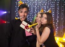 Trois jeunes hommes et deux femmes ont l'amusement dans une boîte de nuit Photographie stock