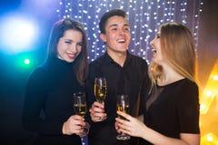 Trois jeunes hommes et deux femmes ont l'amusement dans une boîte de nuit Images stock