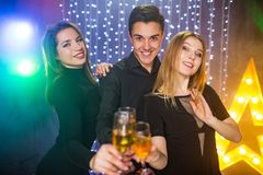 Trois jeunes hommes et deux femmes ont l'amusement dans une boîte de nuit Photos stock