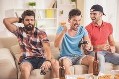 Trois jeunes hommes heureux jouant des jeux vidéo à la maison images libres de droits