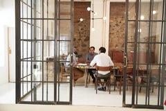 Trois jeunes hommes lors d'une réunion dans une salle de réunion photos stock