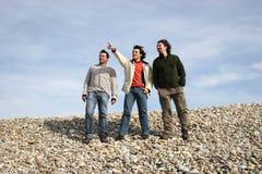 Trois jeunes hommes occasionnels à la plage Image stock