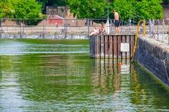 Trois jeunes hommes sans chemise les prennent un bain de soleil sur le dock de natation chez Shadw Image stock