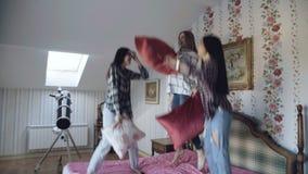Trois jeunes jolies filles sautant sur des oreillers de lit et de combat ayant l'amusement à la maison banque de vidéos