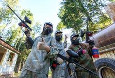 Trois joueurs de paintball avec la grenade fumigène posant dans les masques Photo stock