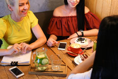 Trois le beau sourire femelle en café, entretien, indiquent des secrets, mangent, d Photographie stock