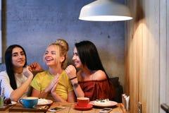 Trois le beau sourire femelle en café, entretien, indiquent des secrets, mangent, d Images stock