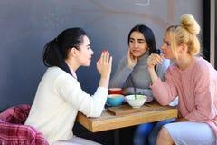 Trois le beau sourire femelle en café, entretien, indiquent des secrets, mangent, d Image stock