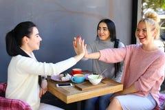 Trois le beau sourire femelle en café, entretien, indiquent des secrets, mangent, d Images libres de droits