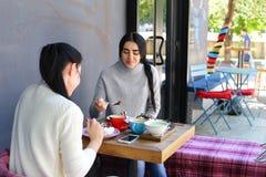 Trois le beau sourire femelle en café, entretien, indiquent des secrets, mangent, d Photo stock