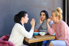 Trois le beau sourire femelle en café, entretien, indiquent des secrets, mangent, d Photos stock