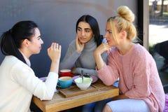 Trois le beau sourire femelle en café, entretien, indiquent des secrets, mangent, d Photo libre de droits