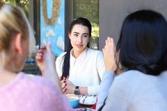 Trois le beau sourire femelle en café, entretien, indiquent des secrets, mangent, d Photos libres de droits
