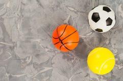 Trois le nouveaux football et basket-ball et balles de tennis en caoutchouc mous sous la forme de triangle sur le vieux ciment us photo stock