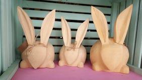 Trois lièvres en bois de Pâques dans une cage Photographie stock