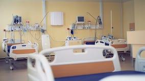 Trois lits à roues sont montrés dans une chambre d'hôpital moderne banque de vidéos