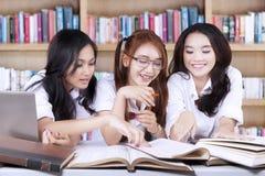 Trois livres de lecture d'étudiants dans la bibliothèque Photos libres de droits