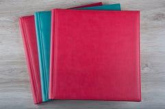 Trois livres en cuir étendus sur la table en bois Images stock